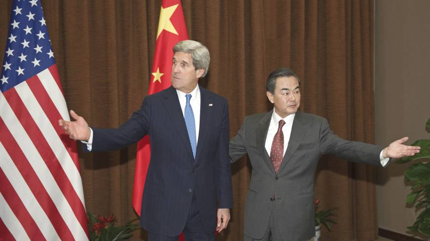 Here and there: U.S. Secretary of State John Kerry and Chinese Foreign Minister Wang Yi are seen in Beijing on Saturday.