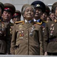 Keeping a close watch: Retired North Korean service members stand at attention during an induction ceremony for the Korean Children's Union, the first political organization North Korea's youths join, at a stadium in Pyongyang on Friday. | AP
