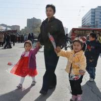 North Korean children carry flowers on the day before the 101st anniversary of the birth of the country's founder Kim Il Sung. | KYODO