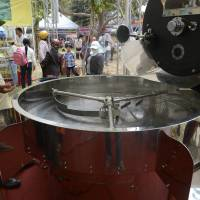 To buy or not to buy: A Vietnamese coffee farmer checks out a coffee roasting machine at a local festival in Buon Ma Thuot, the capital of Dak Lak Province, in mid-March. | AFP-JIJI