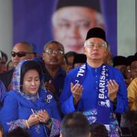 Praying to win: Malaysian Prime Minister Najib Razak (second from right) and his wife offer prayers before leaving for an election nomination center in Pahang state on Saturday. | AP
