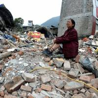 Reduced to rubble: A woman whose relatives were killed in Saturday's earthquake cries while sitting on a pile of rubble in Lingguan township in Baoxing County in southwest China's Sichuan Province on Sunday. | AP