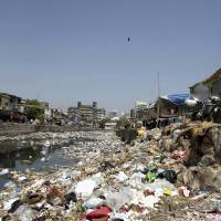 Just a litter bit: A woman throws waste into a garbage-choked Mumbai canal on Monday. | AP