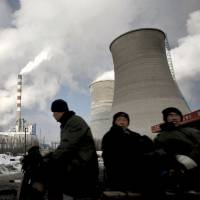 Burning calories: Workers ride past a coal-fired power plant on a tricycle cart in Changchun, in northeast China's Jilin Province, in December 2010. | AP