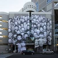 Facing reality: French artist JR's portraits of people from Tohoku wallpaper the front of the Watari-um. | PHOTOS COURTESY OF WATARI-UM