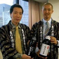 Fermenting change: Toshifumi Imai (above right), the executive director of Kamenoi Shuzo in Yamagata Prefecture, with his father, Shunji, the president, show off their 'Super' Kudoki Jozu Junmai Daiginjo. | MELINDA JOE / COURTESY OF HACHINOHE SHUZO