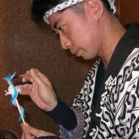 Eye candy: Takahiro Mizuki is a master of traditional ame zaiku (candy sculpture). Here, at a recent society event in an upscale Tokyo hotel, he coaxes his current masterpiece creation, a bi-colored candy-clawed dragon, from its scalding raw material of boiled starch sugar. | KIT NAGAMURA PHOTO