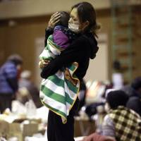 Especially vulnerable: A woman holds her child at a shelter in Fukushima city after being evacuated from an area near the Fukushima No. 1 nuclear plant a few days after the March 11, 2011,  earthquake and tsunami. | AP
