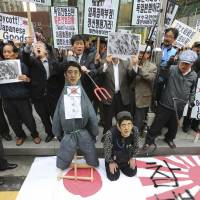 Keeping the fire stoked: Members of South Korean conservative civic groups prepare to burn an effigy of Prime Minister Shinzo Abe in front of the Japanese Embassy in Seoul on  Thursday as part of a protest against visits by a record number of Japanese lawmakers last week to  Tokyo's contentious  Yasukuni Shrine. | AP