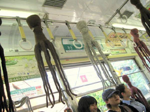 Octopus attack! Knitted octopuses dangle from handrails as a band (below, left) entertains passengers on a street car running through Arakawa in Tokyo. © TAKOYAMA | © TAKOYAMA