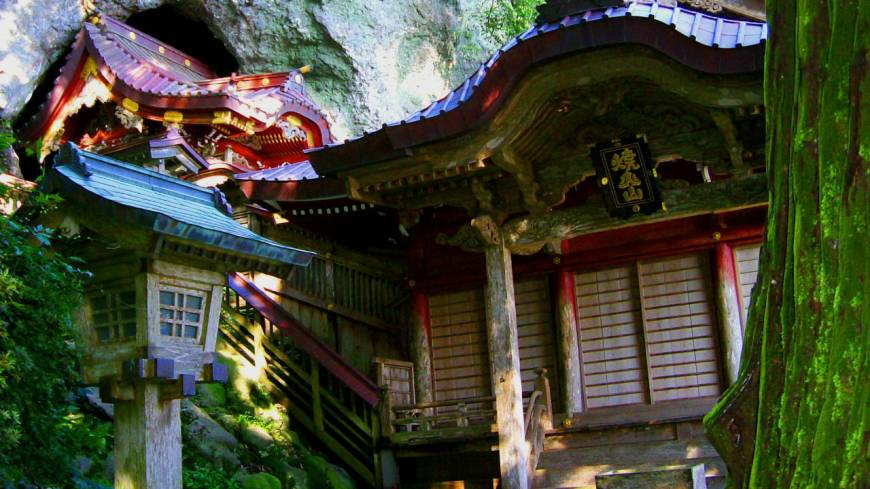 Ancient Takuhi Shrine that emerges from a hilltop cave.