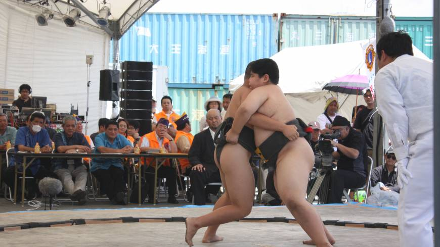 Young sumo wrestlers tussle after both getting <i>mawashi</i> (belt) grips.