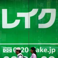 Job insecurity: Pedestrians walk past an advertisement last July for Lake, a former General Electric consumer lending unit now renamed and under the wing of Shinsei Bank. | BLOOMBERG PHOTO