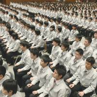 Punch the clock: New recruits at shoe polish maker Columbus shine senior employees' shoes to learn how to use its products at company headquarters in Tokyo on Monday. Left: New Toyota Motor Corp. hires attend an induction ceremony in Toyota, Aichi Prefecture, the same day. | AFP-JIJI, KYODO