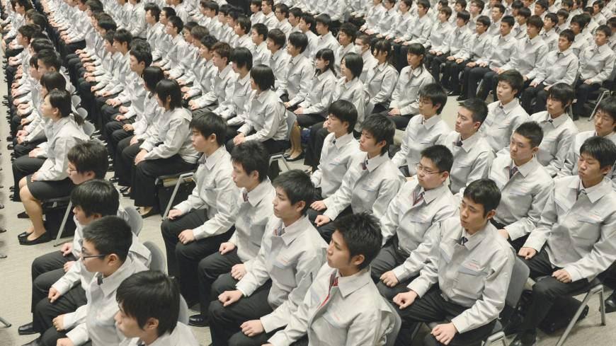 Punch the clock: New recruits at shoe polish maker Columbus shine senior employees' shoes to learn how to use its products at company headquarters in Tokyo on Monday. Left: New Toyota Motor Corp. hires attend an induction ceremony in Toyota, Aichi Prefecture, the same day.