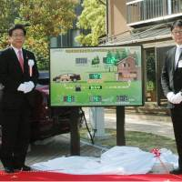 Home appliance: Kitakyushu Mayor Kenji Kitahashi (left) and Yoshiharu Yamamoto, Honda Motor Co. senior managing officer and director, demonstrate the carmaker's home power supply system based on fuel-cell cars Tuesday in the city. | KYODO