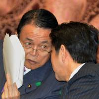 On the same page: Finance Minister Taro Aso (left) confers with Prime Minister Shinzo Abe during the Lower House Budget Committee session Tuesday. | AFP-JIJI