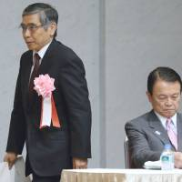 Entrusted: Bank of Japan Gov. Haruhiko Kuroda heads past Finance Minister Taro Aso to the podium Monday at the annual Trust Companies Association of Japan meeting in Tokyo. | BLOOMBERG