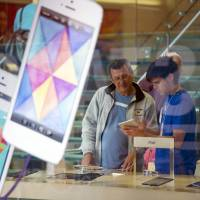 Kid's play: An Apple salesperson shows an iPad to a customer at an Apple Inc. store in San Francisco. | BLOOMBERG