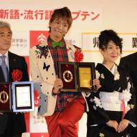 Abuzz: Eiji Ueda (left), chairman of the female soccer committee of the Japan Football Association, and comedian Tanoshingo show off plaques for buzzwords they helped spread this year at a ceremony Thursday in Tokyo. | KYODO PHOTO