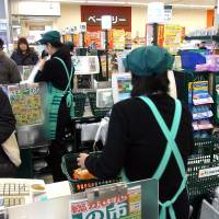 Cash or charge?: Female part-time workers man the checkout lines at a supermarket in Nakano Ward, Tokyo, on Friday. | SATOKO KAWASAKI PHOTO
