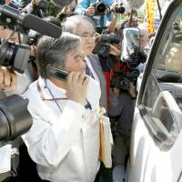 Strong signal: An Okinawa Prefectural Government official makes a phone call to order that a vehicle carrying an environmental assessment report on relocating the U.S. Futenma base turn back amid strong protests from citizens. | KYODO