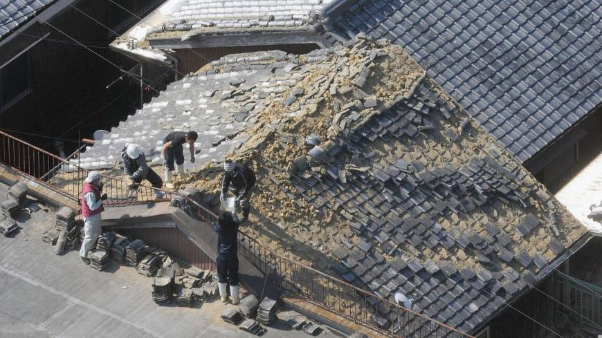 Workmen in Sumoto, Hyogo Prefecture, remove shingles from a roof damaged by the 6M quake that struck western Japan early Saturday morning.