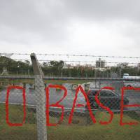 Base desires: A slogan opposing U.S. Marine Corps Air Station Futenma is seen on the fence enclosing the base in Ginowan, Okinawa Prefecture, on Nov. 30. | AP