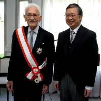 Abdelmalek Benhabyles (left) is bestowed the Grand Cordon of the Order of the Rising Sun by Japanese Ambassador Tsukasa Kawada in Algiers on Dec. 17. Below: Benhabyles (right) with Japanese supporter of Algeria Tokusaburo Dan in 1962. | EMBASSY OF ALGERIA