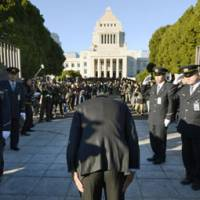 A new day: A lawmaker bows before passing through the gates to the Diet building Wednesday morning. | KYODO