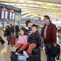 Outward bound: Children ride a luggage cart at Kansai International Airport in Osaka Prefecture as their family prepares to depart Saturday for the New Year's holidays, and as the outbound rush of travelers returning to their hometowns or catching flights to overseas destinations peaked. | KYODO