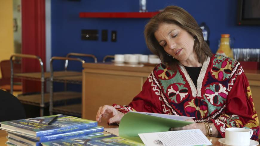 Tokyo-bound?: Caroline Kennedy flips through her new book 'Poems to Learn by Heart' during an interview in New York on March 26.