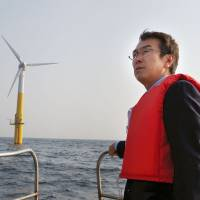 Tailwinds: Environment Minister Nobuteru Ishihara inspects an offshore floating wind turbine on March 9 off the island of Kabashima in Nagasaki Prefecture. | KYODO