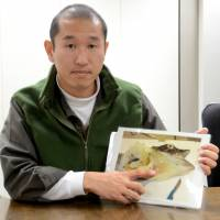 Naoaki Kawahara, a fish keeper at the aquarium, uses a photo to explain the fish's anatomy on Dec. 14. | KYODO
