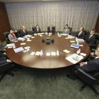 Uncharted waters: Members of the Bank of Japan Policy Board gather at BOJ headquarters Thursday morning for the second day of BOJ Gov. Haruhiko Kuroda's (center) first policy meeting. | KYODO