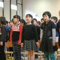 Unified: Kids in Otsuchi Elementary School in Iwate Prefecture sing their new school song Thursday in a gym in a makeshift building. | KYODO