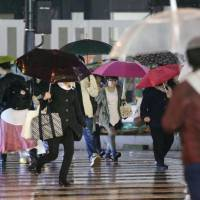 Spring storm: People head toward Shinjuku Station amid heavy rainfall and strong winds Saturday night in Tokyo. | KYODO