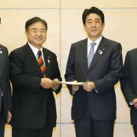 Accepted: Prime Minister Shinzo Abe (second from right) receives a set of education reform proposals from Toshiaki Endo (second from left), head of the ruling Liberal Democratic Party's education panel, on Monday at Abe's office in Tokyo. | KYODO