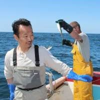 Freshly sourced: Yoshinori Ishii, head chef at the UMU restaurant in London, fishes for mackerel off Cornwall, southwestern England, last May. | KYODO