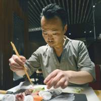Freshly sourced: Yoshinori Ishii, head chef at the UMU restaurant in London, fishes for mackerel off Cornwall, southwestern England, last May, and prepares sashimi at his establishment recently. | KYODO