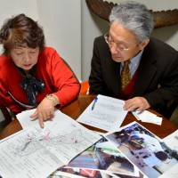 For the fallen: Heitaro Matsumoto and his colleague, Sumiko Naito, who have volunteered to repatriate the remains of fallen Japanese soldiers, show documents of their work during an interview in Tokyo on Feb. 5. | AFP-JIJI