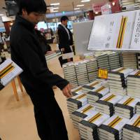 While they last: Customers at the Yurakucho district Sanseido Bookstore in Chiyoda Ward, Tokyo, snap up Haruki Murakami's latest novel, which went on sale Friday. | SATOKO KAWASAKI