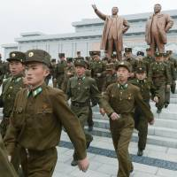Peas in a pod: North Korean soldiers visit the statues of Kim Il Sung and his son, Kim Jong Il, on Mansudae Hill in Pyongyang on Monday to commemorate the birth date of the nation's founder. | KYODO