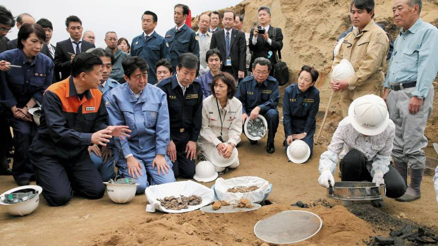 Prime Minister Shinzo Abe inspects work to recover the remains of Imperial Japanese Army soldiers killed in the Battle of Iwojima during his visit to the island Sunday.