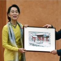 Memento: A University of Tokyo student gives visiting Myanmar democracy icon Aung San Suu Kyi a woodblock print of the school's Akamon gate after she gave a lecture on campus Wednesday morning. | KYODO