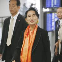 Heading out: Aung San Suu Kyi walks through Narita before leaving for Myanmar on Friday. | KYODO