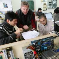 Hands on: Smart Technology Partners founder Carl Sundberg and his staff work Jan. 23 at a data center the firm set up in a vacated elementary school in Aizumisato, Fukushima Prefecture. | KYODO