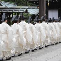 Carrying on: Shinto priests walk to the main shrine in Yasukuni Shrine to perform a rite on the first day of its annual spring festival in Tokyo on Sunday. | AFP-JIJI