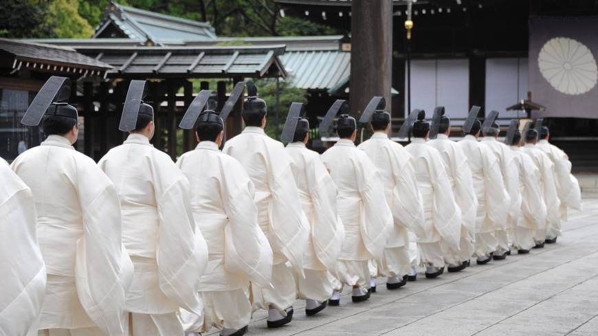 Carrying on: Shinto priests walk to the main shrine in Yasukuni Shrine to perform a rite on the first day of its annual spring festival in Tokyo on Sunday.