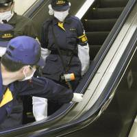 Hands off: Police examine a damaged escalator at JR Akihabara Station in Tokyo that injured six people on Wednesday morning. | KYODO